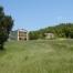 Masia aillada envoltada de boscos i grans extensions de camp. La foto mostra la casa y el paisatje.