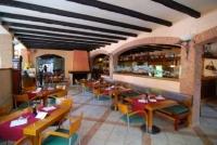 Restaurant amb cuina internacional molt acollidor, amb una gran terrassa sota palmeres.
