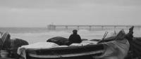 Pescador a la platja de Badalona i el pont del petroli.