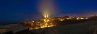 panoràmica nocturna del poble de Guàrdia de Noguera, un dia d'hivern amb boira, al fons la serra dle Montsec